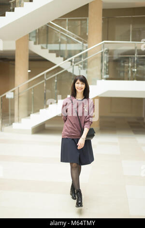 mature woman walking confidently in mall while looking at camera - Stock Photo