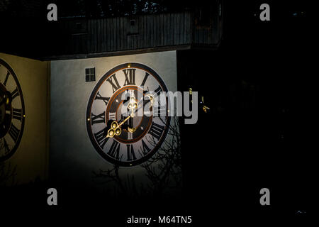 Close up of the Graz clock tower with its golden hands indicating the hour - Stock Photo
