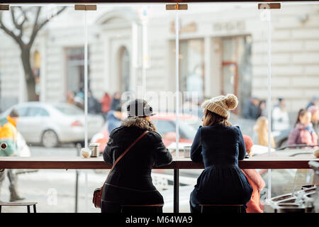 Two woman sit on the table at coffee place and talk to each other - Stock Photo