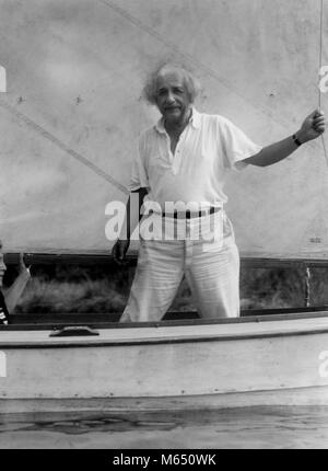 Portrait of scientist Albert Einstein smiling, standing and holding a rope while relaxing and sailing on a small - Stock Photo