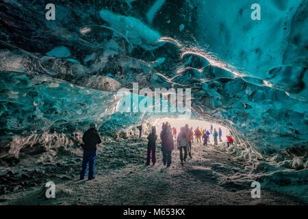Tourists in The Crystal Cave, Breidamerkurjokull Glacier, Iceland. Emerald Blue Ice and Ash is part of Breidamerkurjokull. - Stock Photo