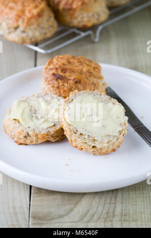 Freshly baked cheese scones spread with butter.
