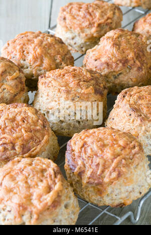 Freshly baked cheese scones cooling on a wire tray. - Stock Photo