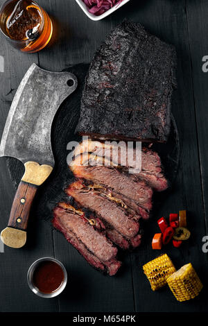 Fresh Brisket BBQ beef sliced for serving against a dark background with sauce, hot peppers and corn. - Stock Photo