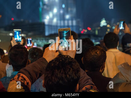 31th December 2017 - Dubai, UAE. Men records laser show on his smart phone at Burj Khalifa. People celebrating new - Stock Photo