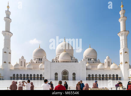 28th December 2017 - Abu Dhabi, UAE. Tourists take photographs and selfies in front of a gorgeous Sheikh Zayed mosque. - Stock Photo