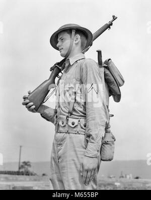 1940s AMERICAN SOLDIER RIFLE ON SHOULDER WEARING HELMET KHAKI UNIFORM WITH PRIVATE FIRST CLASS STRIPE ON SLEEVE - Stock Photo