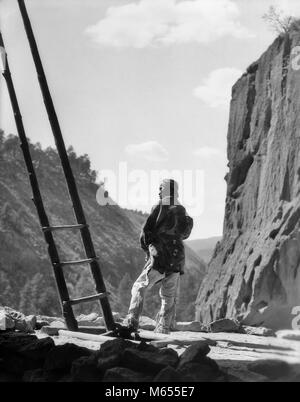 1930s NATIVE AMERICAN INDIAN MAN BY KIVA LADDER FRIJOLES CANYON CEREMONIAL KIVA BANDELIER NATIONAL MONUMENT NEW - Stock Photo