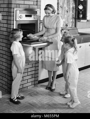 1950s MOTHER AND THREE DAUGHTERS STANDING AROUND OVEN IN KITCHEN BAKING PIE - asp_x16744 CAM001 HARS HEALTHINESS - Stock Photo