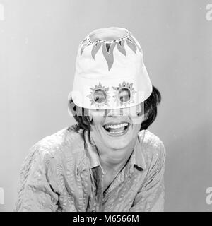 1960s SMILING WOMAN WEARING FUNNY WACKY SUN HAT WITH SUNSPOTS FOR EYEGLASSES LOOKING AT CAMERA - c10634 HAR001 HARS - Stock Photo