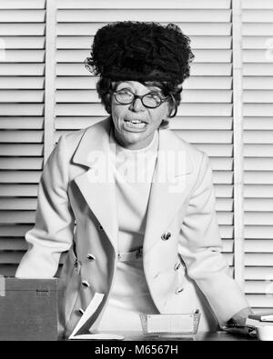 1970s CRAZY BUSINESSWOMAN AT OFFICE DESK WEARING HAT EYEGLASSES DISHEVELED ANGRY FACIAL EXPRESSION LOOKING AT CAMERA - Stock Photo