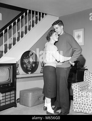 1950s HUGGING DANCING TEENAGE COUPLE IN LIVING ROOM - d3720 HAR001 HARS FRIENDSHIP FULL-LENGTH HUG BOYFRIEND CARING - Stock Photo