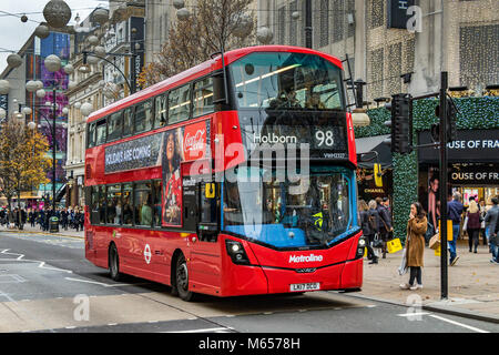 A  woman waits to cross at a pedestrian Crossing as a No98 London Bus to Holborn makes it's way along Oxford St - Stock Photo