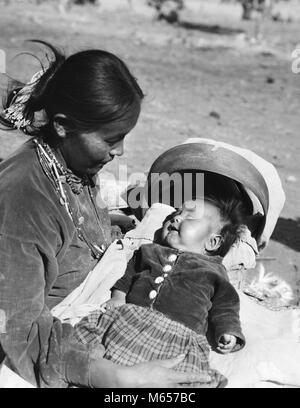 1930s NATIVE AMERICAN NAVAJO INDIAN WOMAN MOTHER HOLDING SMILING BABY PAPOOSE IN CRADLE BOARD - i1125 HAR001 HARS - Stock Photo