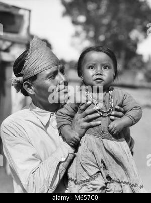 1930s PROUD NATIVE AMERICAN INDIAN NAVAJO MAN FATHER HOLDING BABY GIRL DAUGHTER LOOKING AT CAMERA - i1138 HAR001 - Stock Photo
