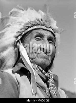 1950s 1960s PORTRAIT NATIVE AMERICAN CHEROKEE INDIAN SENIOR MAN WEARING FEATHER HEADDRESS LOOKING AT CAMERA NORTH - Stock Photo