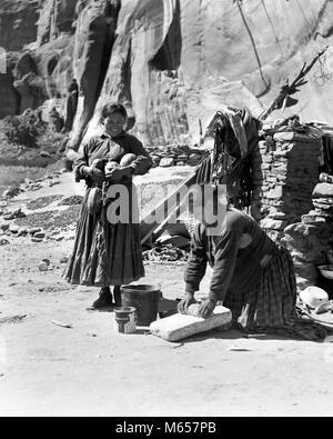 1930s TWO NATIVE AMERICAN NAVAJO INDIAN WOMEN GRINDING CORN AND HARVESTING SQUASH CANYON DEL MUERTO ARIZONA USA - Stock Photo