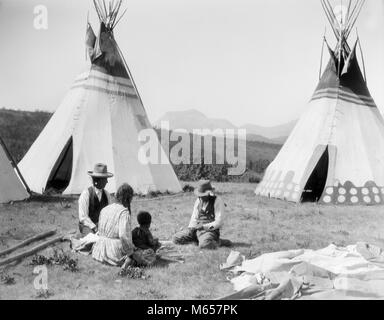 1920s NATIVE AMERICAN INDIAN FAMILY MAN WOMAN TWO CHILDREN SITTING IN FRONT OF TEPEES SIOUX TRIBE MONTANA USA - - Stock Photo