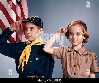 1960s BOY AND GIRL IN CUB SCOUT AND BROWNIE UNIFORMS STANDING BY AMERICAN FLAG SALUTING - kb2561 HAR001 HARS CELEBRATION - Stock Photo