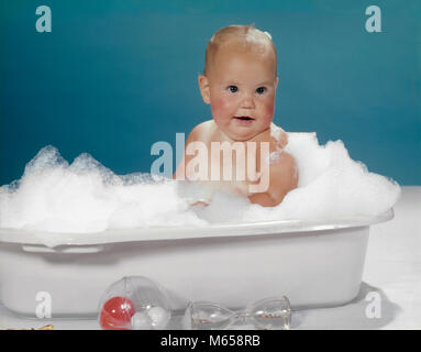 1950s 1960s CLEAN HAPPY BABY SITTING IN PLASTIC BATH TUB BASIN FULL OF SOAP SUDS - kb3222 HAR001 HARS HAPPINESS - Stock Photo
