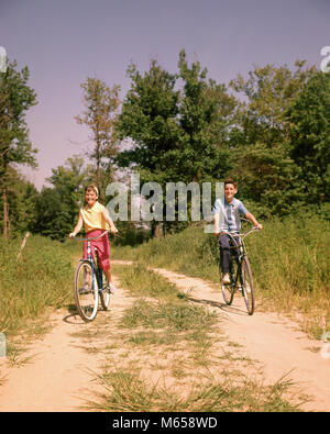 1960s BOY AND GIRL RIDING BIKES ON COUNTRY LANE IN SUMMERTIME LOOKING AT CAMERA - kb3790 HAR001 HARS RURAL HOME - Stock Photo