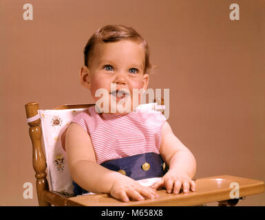 1960s BABY SITTING IN HIGHCHAIR SMILING LOOKING AT CAMERA - kb4317 HAR001 HARS INDOORS NOSTALGIA EYE CONTACT 0-1 - Stock Photo