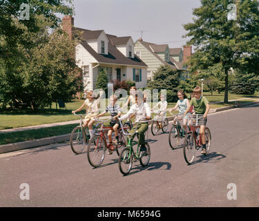 1960s 1970s GROUP OF 7 CHILDREN RIDING BIKES DOWN SUBURBAN STREET - kb7276 HAR001 HARS PRETEEN BOY HAPPINESS NEIGHBORHOOD - Stock Photo