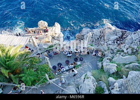 People relaxing and having drinks in a bar located on rocks by the sea, Dubrovnik, Dalmatia, Croatia - Stock Photo
