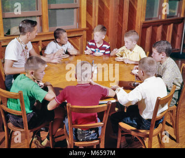 1960s YOUNG TEENAGE MAN CAMP COUNCILOR SITTING AT WOODEN ROUND TABLE EATING ICE CREAM TALKING WITH SEVEN KIDS BOY - Stock Photo