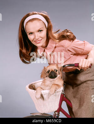 1960s SMILING WOMAN LOOKING AT CAMERA LEANING ON HANDLEBARS OF BICYCLE PET PUG DOG IN BASKET - kd2011 HAR001 HARS - Stock Photo