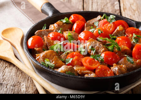 Spicy roast beef with tomatoes and greens close-up on a frying pan on a table. horizontal - Stock Photo