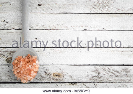 Course Grind Pink Himalayan Salt on a Blue Wooden Spoon on a White Distressed Wooden Background with Copy Space. - Stock Photo