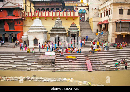 KATHMANDU, NEPAL - MAY 18: Cremation ceremony along the holy Bagmati River at Pashupatinath Temple complex, May - Stock Photo
