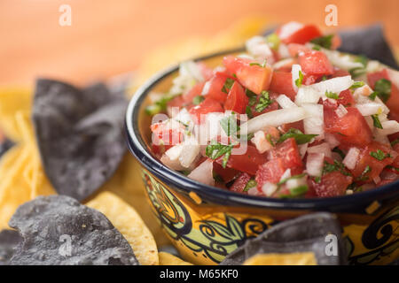 Pico De Gallow in a traditional ceramic bowl with blue corn and white corn tortilla chips - Stock Photo