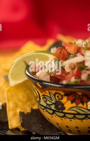 Pico De Gallo in a pretty Ethnic bowl with blue corn and white corn tortilla chips against red background - Stock Photo