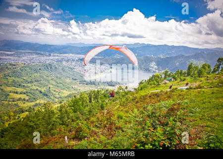 POKHARA, NEPAL -MAY 25, 2013: Paraglider Paragliders take off from Sarangkot on May 25, 2013 in Pokhara, Nepal.The - Stock Photo