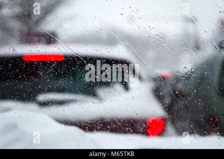 closeup of snowflakes and drizzle on windshield car driving through heavy winter city highway traffic with rear - Stock Photo