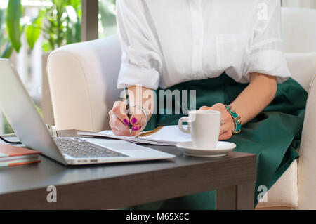 Business woman writing and using computer in office. Business concept. - Stock Photo