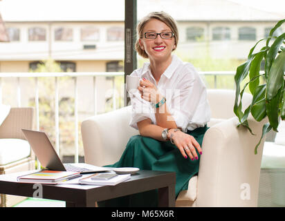 Happy business woman drinks coffee, enjoying espresso sitting at her working place in office - Stock Photo