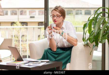 Business woman drinks coffee, enjoying espresso sitting at her working place in office