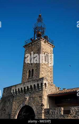 Close-up of old stone tower at sunrise, with clock and bell, in the city center of the quiet village of Le Thor. - Stock Photo