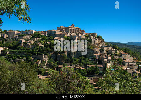 Panoramic view of the village of Gordes on top of a hill and under sunny blue sky. Located in the Provence region, - Stock Photo