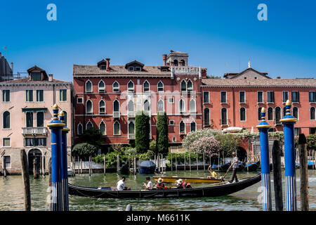 Gondolier riding his gondola, taking tourists for a Grand Canal city sightseeing tour. Magical Venice, Italy, Europe. - Stock Photo