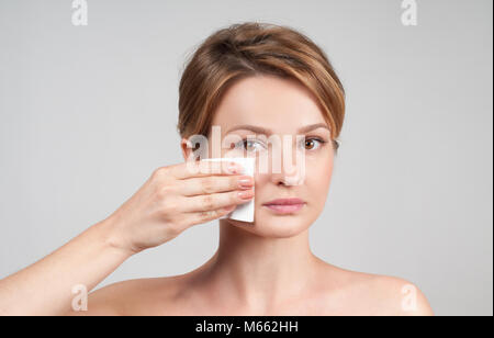 Beauty. Skin care concept. Woman removing makeup from her face with cotton swab pad. - Stock Photo