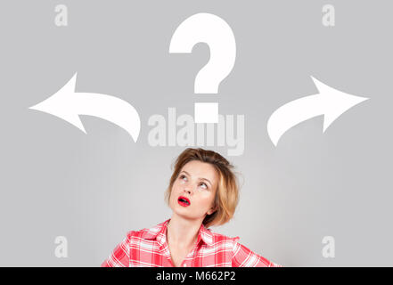 Young woman taking a decision with question mark and arrows above his head - Stock Photo