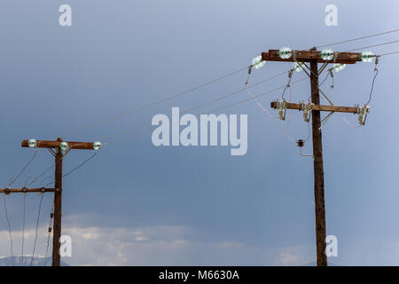 Couple of old wooden electric pillars with copy space between them and power lines against stormy sky - Stock Photo