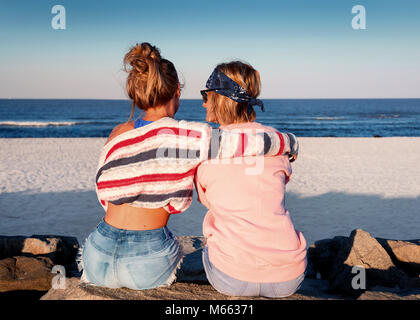 Two young girls, best friends sitting together on the beach at sunset. Friendship, happiness, beach, summer concept - Stock Photo