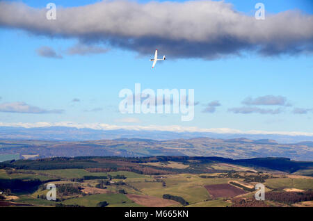 View from the hilltop of East Lomond in Fife looking inland towards the snow capped cairngorm mountains in the distance. - Stock Photo