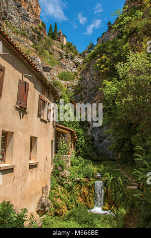 View of houses near creek and bluff with church on cliffs in the charming Moustiers-Sainte-Marie village. In the - Stock Photo