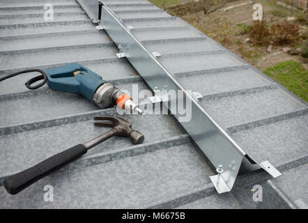It made a barrier to the snow guard on the edge of a metal roof - Stock Photo